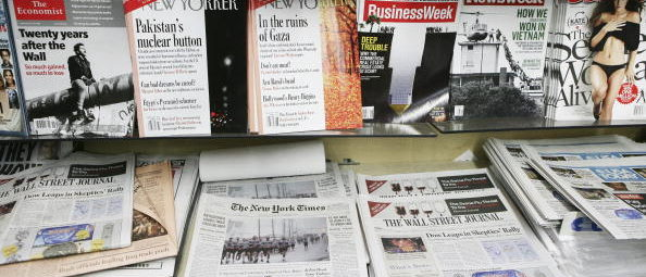Copies of U.S. newspapers including the Wall Street Journal, New York Times, and USA Today sit on display at a news stand with magazines in New York, U.S., on Tuesday, Nov. 10, 2009. U.S. newspaper circulation declines steepened in the six months through September after publishers raised subscription and newsstand prices to help counter an advertising slump. Photographer: Gino Domenico/Bloomberg via Getty Images
