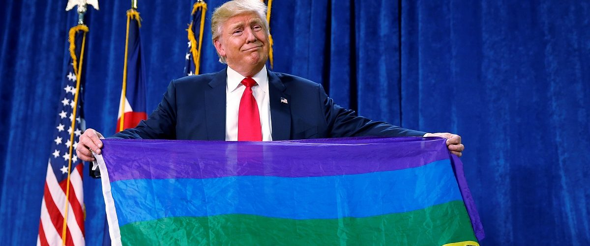 """Republican presidential nominee Donald Trump holds up a rainbow flag with """"LGBTs for TRUMP"""" written on it at a campaign rally in Greeley, Colorado, U.S. October 30, 2016. REUTERS/Carlo Allegri."""