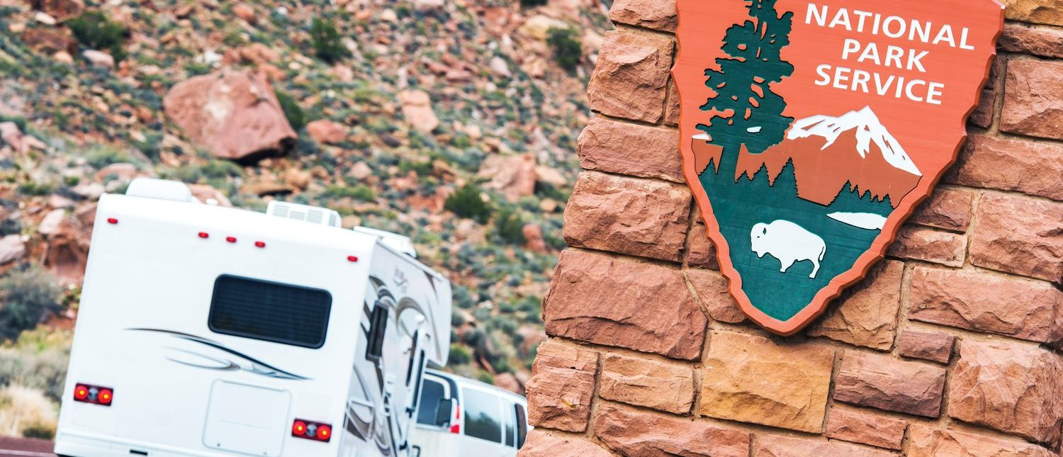American National Parks RV Journey. National Park Service Shield. Zion National Park Entrance. (Shutterstock/welcomia)