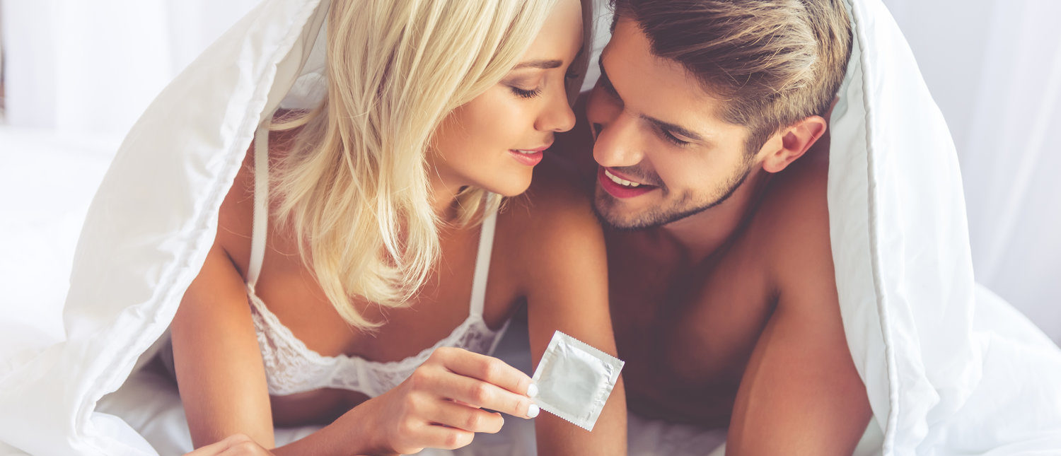 Beautiful young couple is hugging and smiling while lying covered with blanket in bed. Woman is holding a condom (Shutterstock/George Rudy)