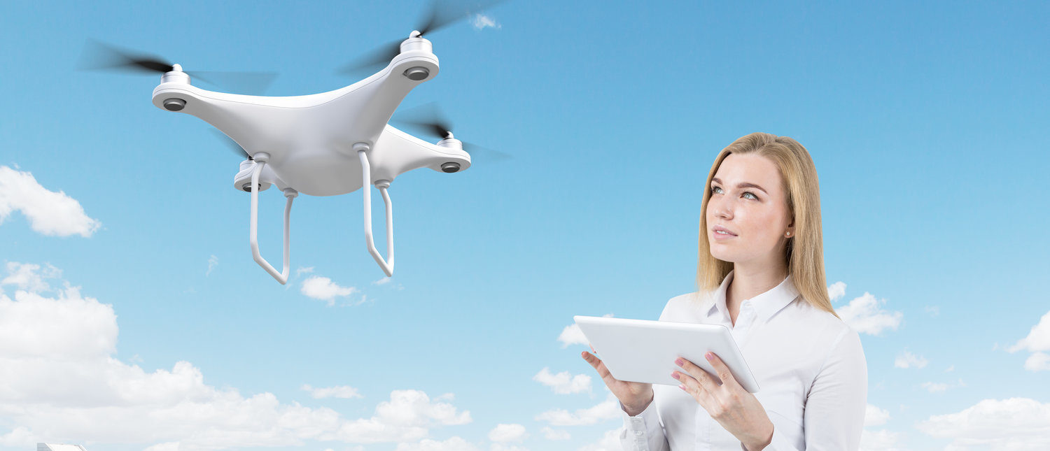 Portrait of blond young woman with tablet computer controlling a drone in large city. Concept of the future is now. 3d rendering. Mock up  (Shutterstock/ImageFlow)