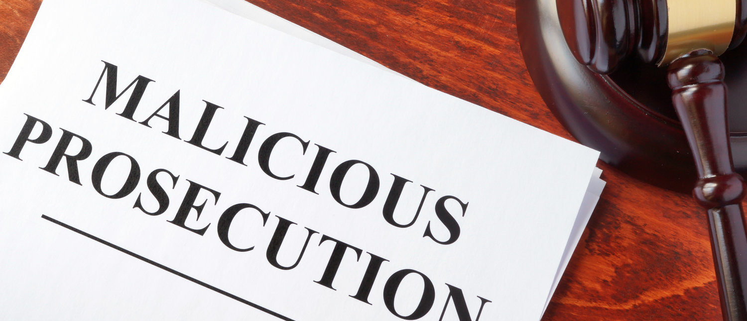 Malicious prosecution, documents and gavel on a table. (Shutterstock/designer491)