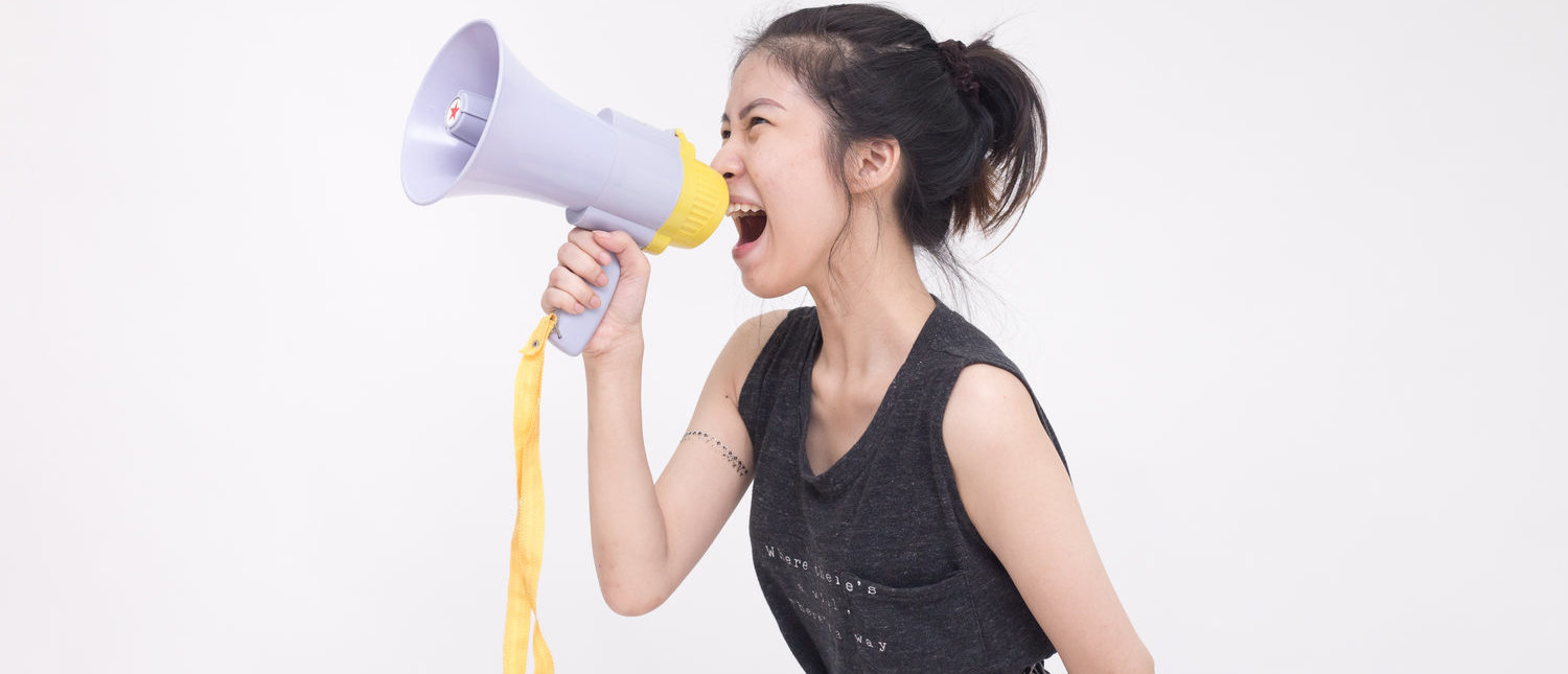 Young woman shouting and screaming with the megaphone (isolated on white background) (Shutterstock/Teerawit Chankowet)