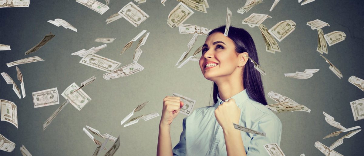Portrait happy woman exults pumping fists ecstatic celebrates success under a money rain falling down dollar bills banknotes isolated on gray wall background with copy space (Shutterstock/pathdoc)