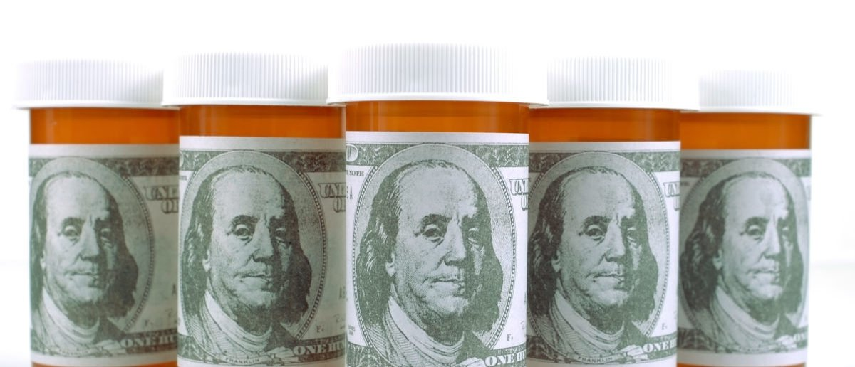 Pill bottles wrapped in money. Shutterstock/Tim Masters