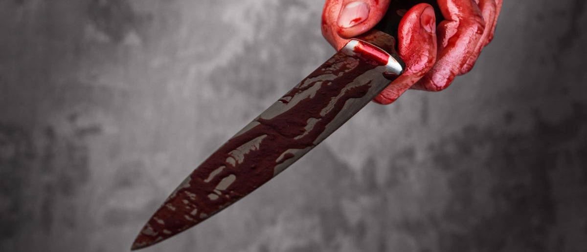A man holds a bloody knife. Source: Shutterstock/BLACKDAY