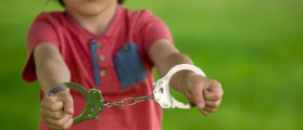 Little boy in handcuffs who was arrested for thievery. [Shutterstock - Tomsickova Tatyana]