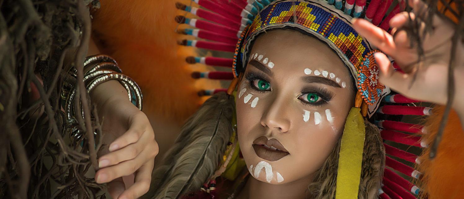 Girl wears a Native American headdress. (Shutterstock/Tanakorn Pussawong)