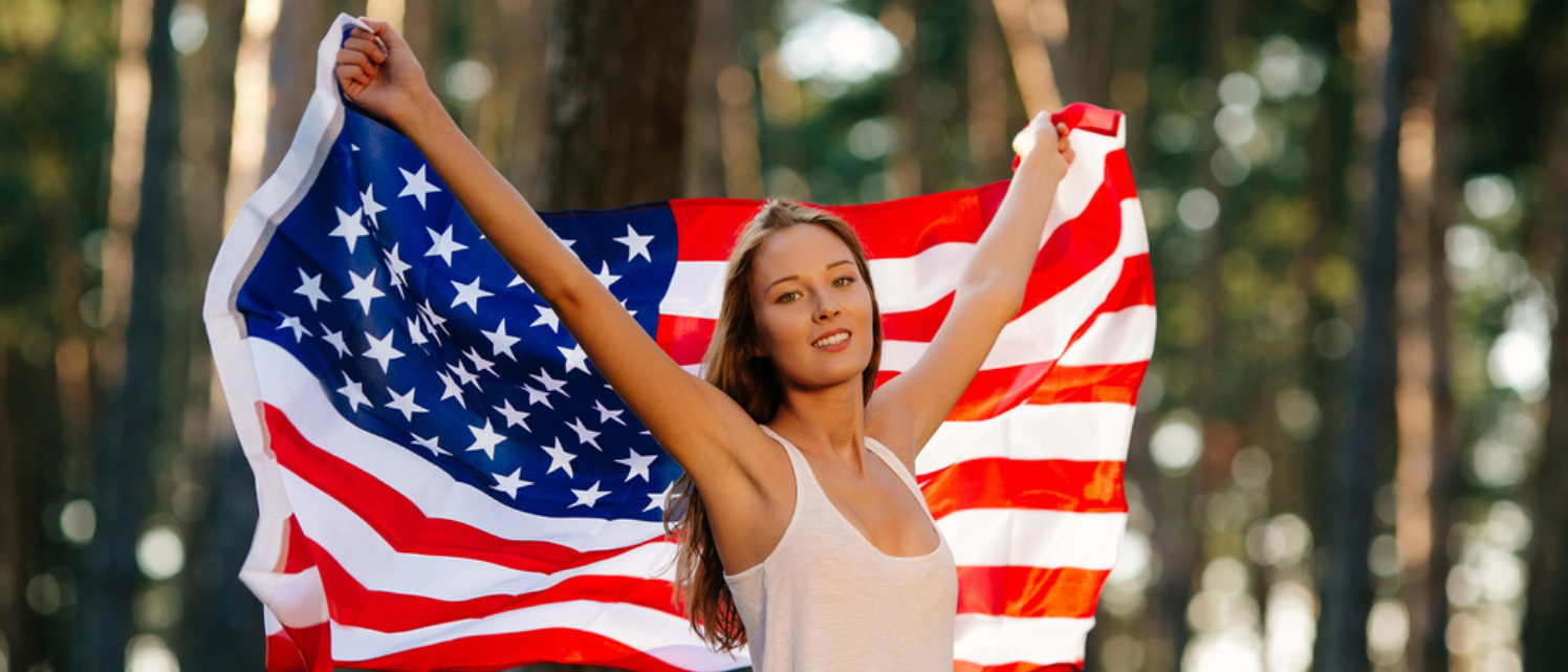 Patriotic woman reveling in the knowledge that America is #1, full-stop.(Shutterstock/Azovtsev Maksym)