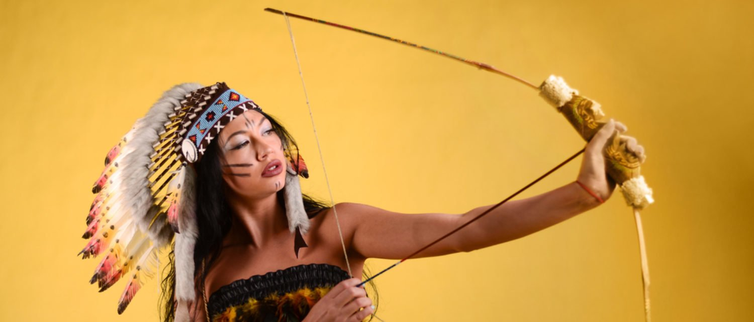 A woman dressed in American Indian garb aims a bow and arrow. (Shutterstock/Vladimir Gappov)