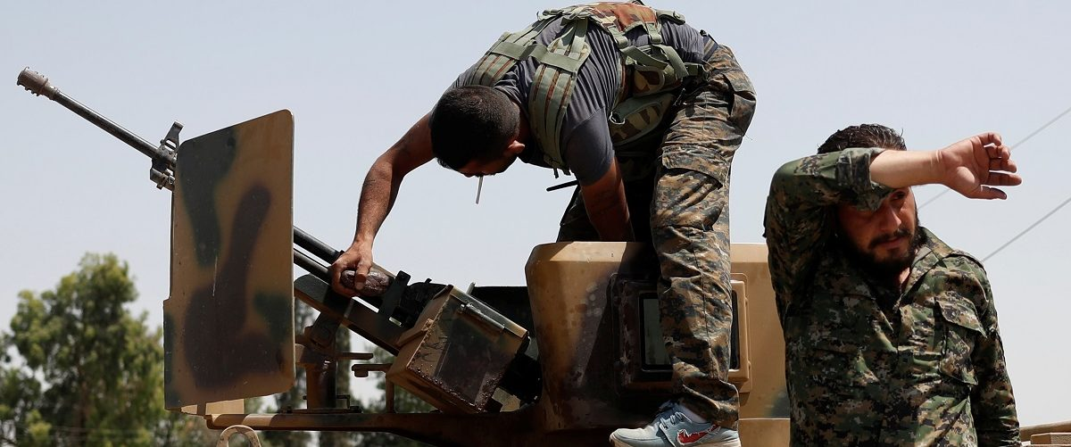 A Kurdish fighter from the People's Protection Units (YPG) adjusts a gun on top of an armored vehicle in Raqqa