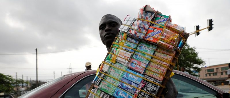 A man selling sweets in traffic holds Nigerian naira along a road near a currency exchange market in Ikeja district in Lagos, Nigeria August 12, 2017. Picture taken August 12, 2017. REUTERS/Akintunde Akinleye