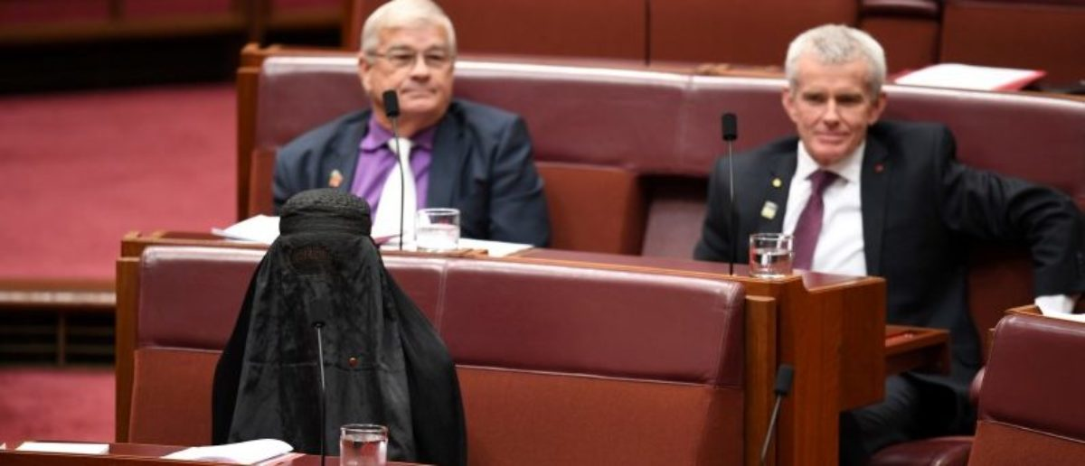 Australian One Nation party leader, Senator Pauline Hanson (L) wears a burqa in the Senate chamber at Parliament House in Canberra, Australia, August 17, 2017. AAP/Mick Tsikas/via REUTERS