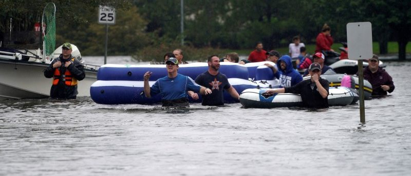People are evacuated by volunteers in waist-deep floodwaters from Hurricane Harvey in Houston, Texas August 29, 2017. REUTERS/Rick Wilking