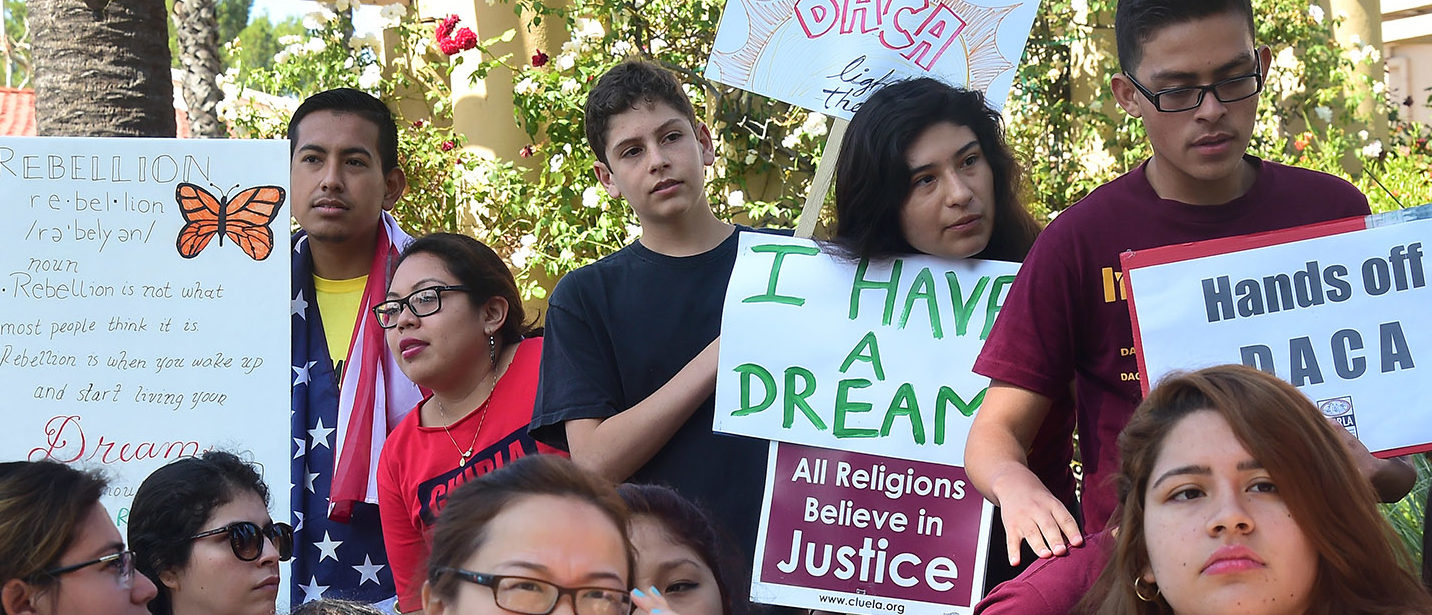 Children hold banners and placards while listening to speakers at a rally outside the 9th Circuit federal court in Pasadena, California on July 16, 2015, where Immigrant rights organizations, labor, and Deferred Action for Childhood Arrivals (DACA) recipients from Arizona and Los Angeles gathered. After a multiple-year legal battle, the state of Arizona's embattled efforts to deny driver's licenses to immigrants who have been granted DACA under a federal program will face what could be yet another blow to Arizona when the Court of Appeals for the Ninth Circuit hears oral arguments this Thursday in a lawsuit brought by civil rights groups challenging the discriminatory policy. PHOTO: Getty Images/AFP/FREDERIC J. BROWN