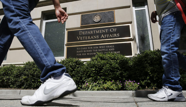 The sign in the front of the headquarters building at the Department of Veteran Affairs is seen as people walk past in Washington, May 23, 2014. REUTERS/Larry Downing
