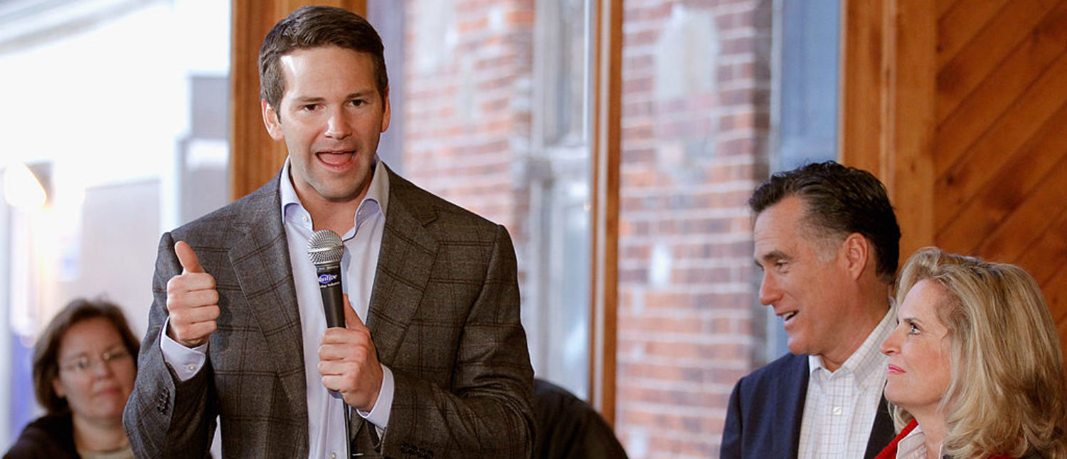 Rep. Aaron Schock (R-IL) (L) tells an audience at Elly's Tea and Coffee why he is endorsing former Republican presidential candidate and former Massachusetts Gov. Mitt Romney (C) during an event with Romney and his wife Ann Romney (R) December 28, 2011 (Photo by Chip Somodevilla/Getty Images)