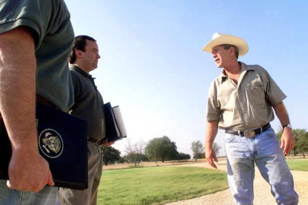 U.S. President George W. Bush talks with Deputy Chief of Staff Joe Hagin and deputy press secretary Scott McClellan on August 6, 2001 at his ranch in Crawford, Texas. (Photo by Eric Draper/White House/Getty Images)