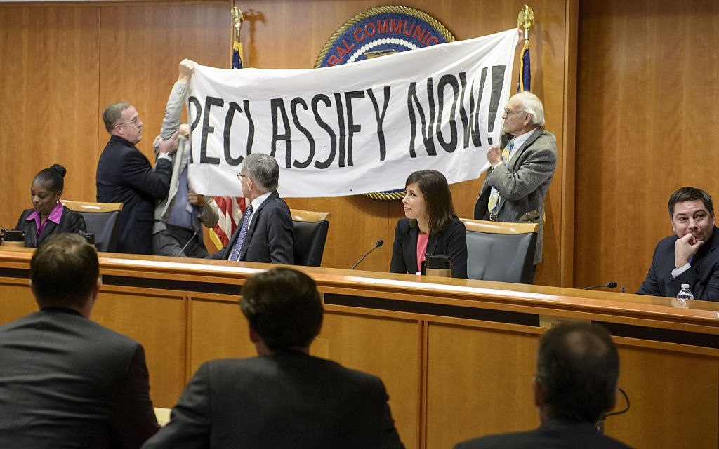 FCC commissioners watch as protesters are removed from the dais during a hearing at the agency's headquarters on December 11, 2014 in Washington, DC. The protesters were advocating for net neutrality. [Brendan Smialowski/AFP/Getty Images]