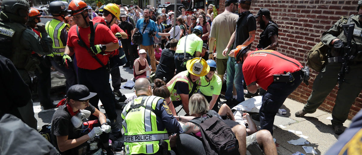 "CHARLOTTESVILLE, VA - AUGUST 12:  Rescue workers and medics tend to many people who were injured when a car plowed through a crowd of anti-facist counter-demonstrators marching through the downtown shopping district August 12, 2017 in Charlottesville, Virginia. The car plowed through the crowed following the shutdown of the ""Unite the Right"" rally by police after white nationalists, neo-Nazis and members of the ""alt-right"" and counter-protesters clashed near Lee Park, where a statue of Confederate General Robert E. Lee is slated to be removed.  (Photo by Chip Somodevilla/Getty Images)"