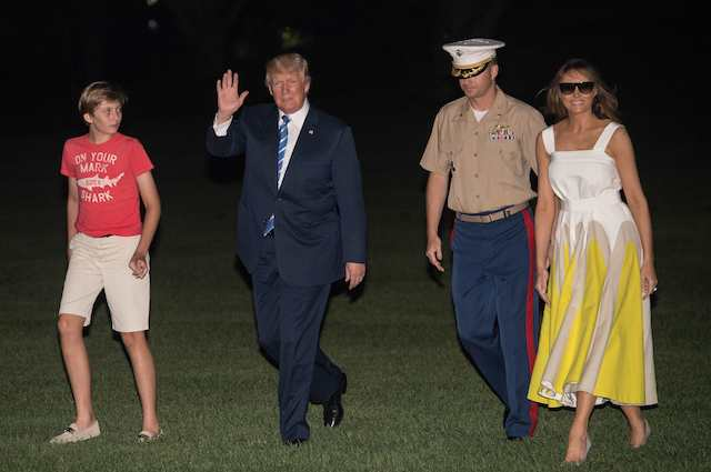 "US President Donald Trump returns to the White House with First Lady Melania Trump and son Barron in Washington, DC, on August 20, 2017 after a 17-day ""working vacation."" / AFP PHOTO / NICHOLAS KAMM (Photo credit should read NICHOLAS KAMM/AFP/Getty Images)"