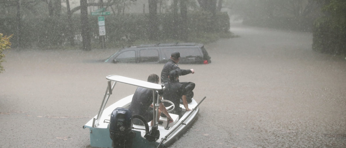 Volunteers and officers from the neighborhood security patrol help to rescue residents in the upscale River Oaks neighborhood (Scott Olson/Getty Images)