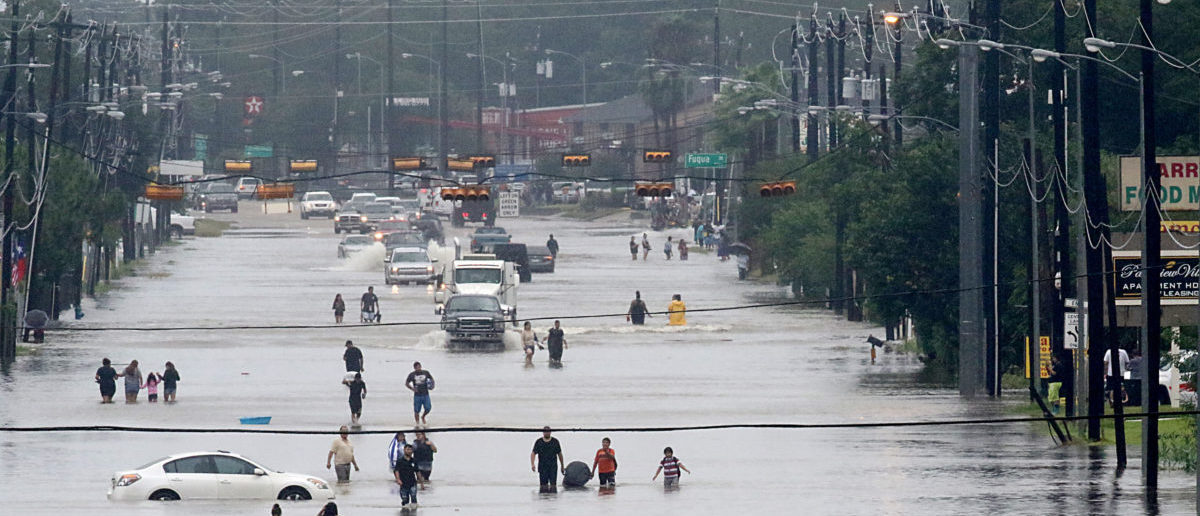 People walk through the flooded waters of Telephone Rd. in Houston on August 27, 2017 as the US fourth city city battles with tropical storm Harvey and resulting floods. / AFP PHOTO / Thomas B. Shea (THOMAS B. SHEA/AFP/Getty Images)