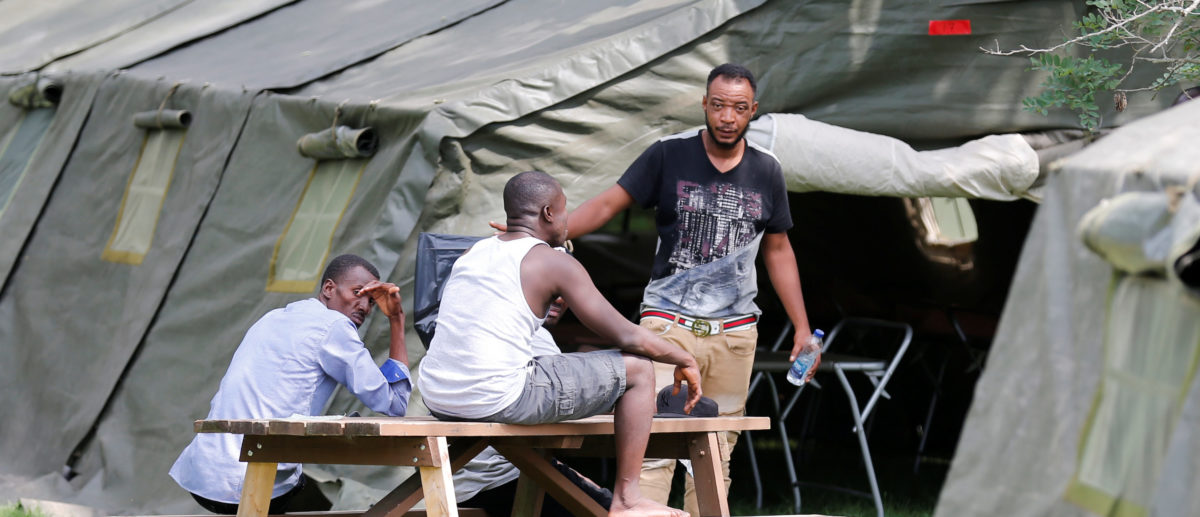 Refugees sit outside one of the tents set up to house the influx of asylum seekers by the Canadian Armed Forces near the border in Lacolle, Quebec, Canada August 10, 2017. REUTERS/Christinne Muschi