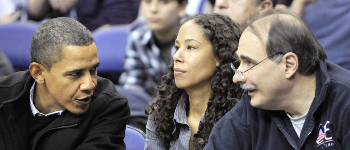 U.S. President Barack Obama (L) talks with Deputy White House Chief of Staff Mona Sutphen (C) and advisor David Axelrod at an NCAA basketball game between Georgetown University and Duke University in Washington January 30, 2010. REUTERS/Jonathan Ernst (UNITED STATES - Tags: POLITICS SPORT BASKETBALL)