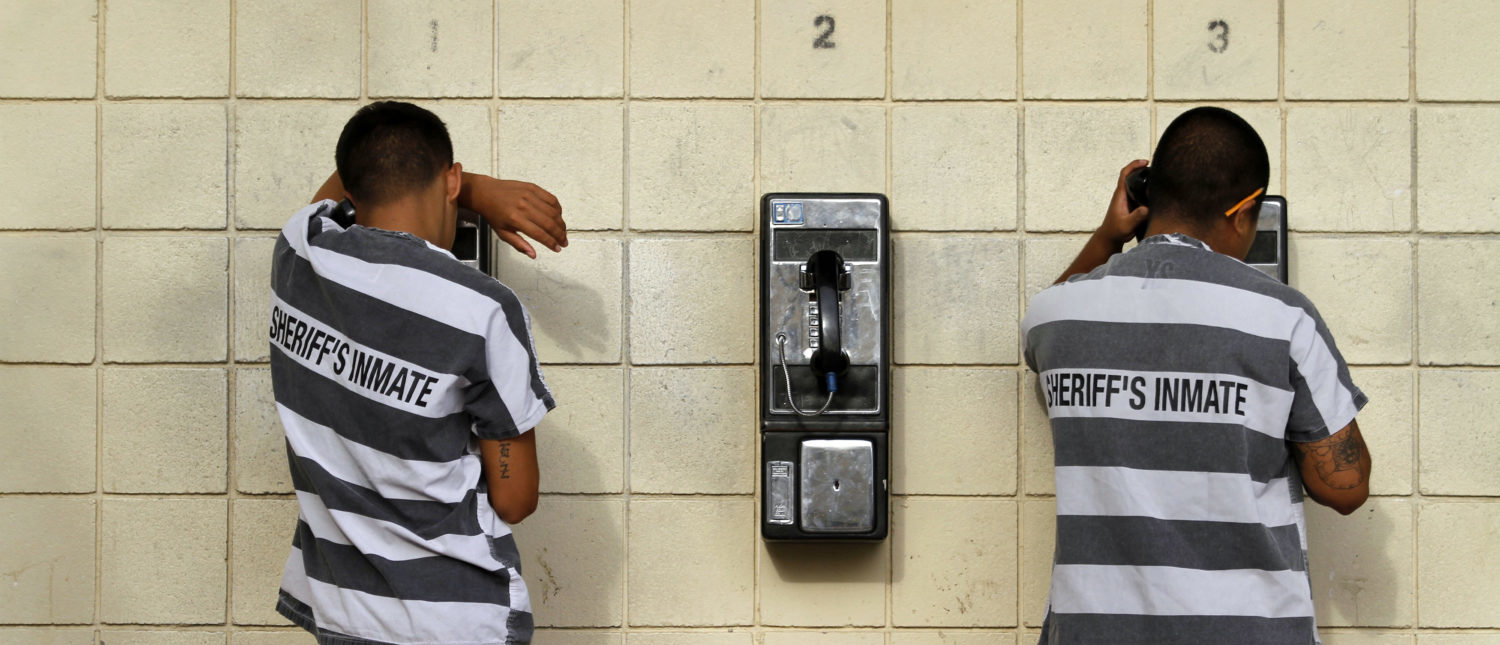 Inmates serving a jail sentence make a phone call at Maricopa County's Tent City jail in Phoenix July 30, 2010. REUTERS/Joshua Lott