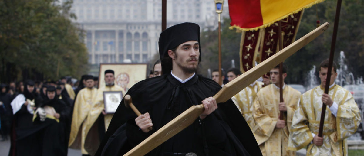 Romanian Orthodox priests attend a religious procession in front of the House of the People, built by late Communist dictator Nicolae Ceausescu, in Bucharest October 24, 2011. Romania's Orthodox church opened a week of pilgrimage to the head of St. Andrew of Patras, Greece, brought on Monday to be worshipped together with the relics of St. Dimitrie Basarabov, the spiritual patron of Bucharest. REUTERS/Bogdan Cristel (ROMANIA - Tags: RELIGION SOCIETY) - RTR2T4UP