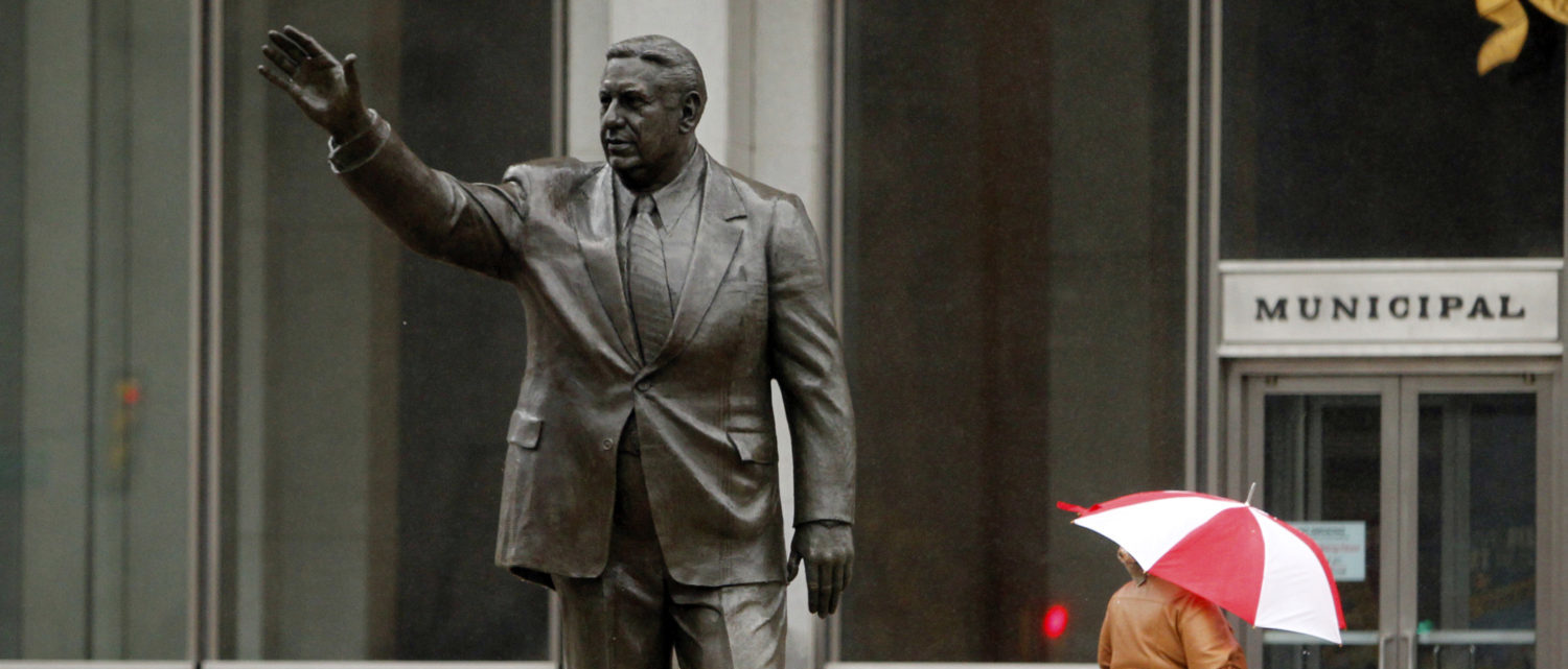 A pedestrian walks past a statue of former mayor Frank Rizzo in wind and rain from Hurricane Sandy in Philadelphia, Pennsylvania, October 29, 2012. Hurricane Sandy, the monster storm bearing down on the U.S. East Coast, strengthened on Monday after hundreds of thousands moved to higher ground, public transport shut down and the U.S. stock market suffered its first weather-related closure in 27 years. REUTERS/Tim Shaffer (United States - Tags: ENVIRONMENT) - RTR39QNU