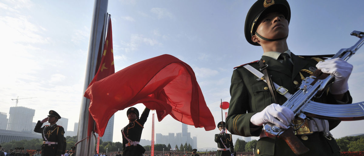 A paramilitary policeman unfurls a Chinese national flag during a flag-raising ceremony to mark the 65th anniversary of the founding of the People's Republic of China, in Hefei, Anhui province October 1, 2014. REUTERS/Stringer