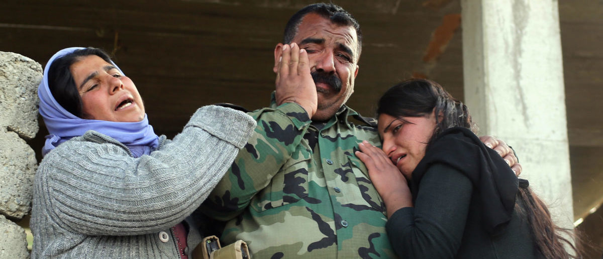 Kurdish Yazidis, relatives of a Peshmerga fighter killed in a suicide attack in Sinjar province, mourn with another relative, also member of the Peshmerga, before the burial ceremony at Mazar Sharaf Eldin, a sacred and cemetery area for the Yazidi minority, north of Sinjar, March 2, 2015. A number of Peshmerga were killed and others injured after two suicide car bombs attacks targeted a building the Peshmerga were using for fighting, according to Peshmerga officials. REUTERS/Asmaa Waguih (IRAQ - Tags: CONFLICT POLITICS CIVIL UNREST MILITARY TPX IMAGES OF THE DAY) - RTR4RTBF