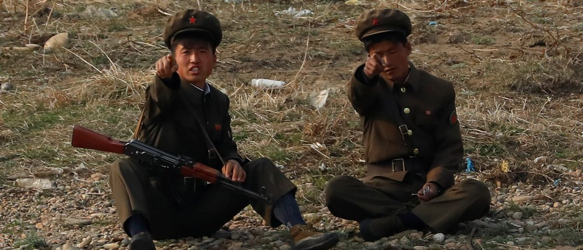 North Korean soldiers gesture at the Yalu River in Sinuiju, North Korea, which borders Dandong in China's Liaoning province, April 15, 2017. REUTERS/Aly Song