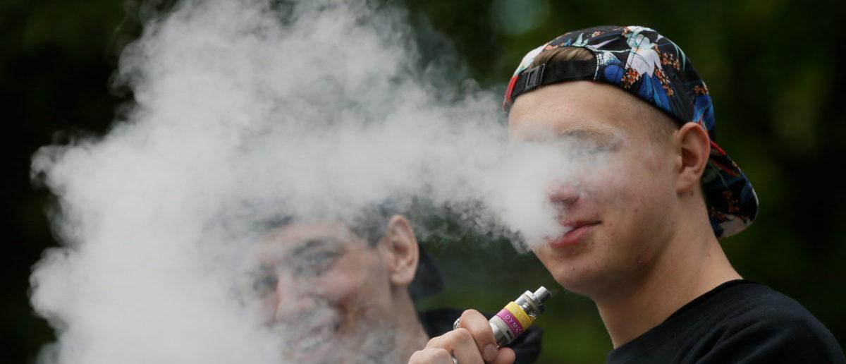 A man exhales electronic cigarette vapour in a park in central Kiev, Ukraine May 12, 2017. REUTERS/Valentyn Ogirenko