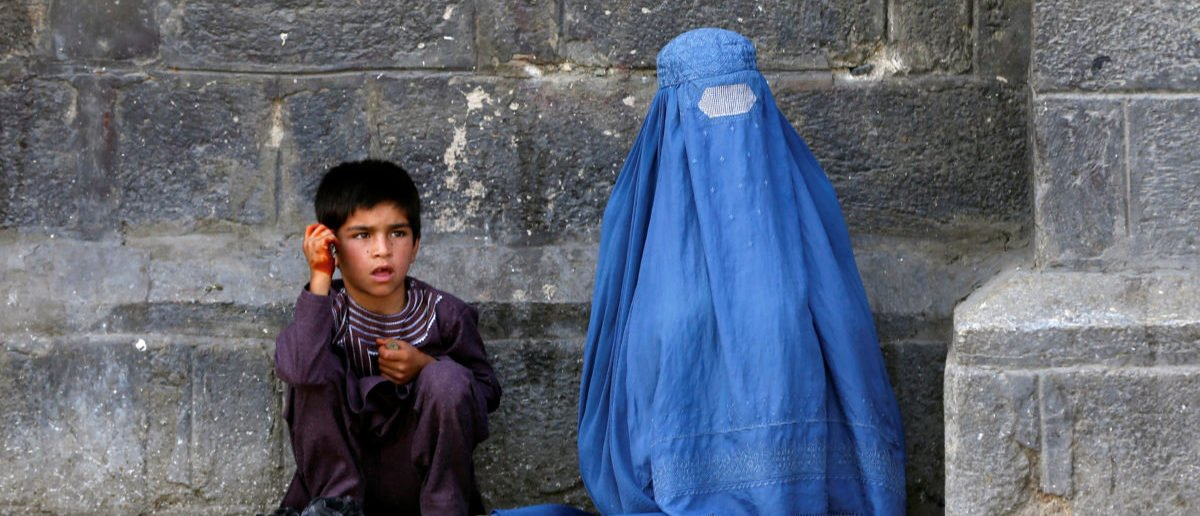 An Afghan woman and her son beg at a mosque on the first day of Eid al-Fitr, which marks the end of the holy month of Ramadan, in Kabul, Afghanistan June 25, 2017. REUTERS/Omar Sobhani