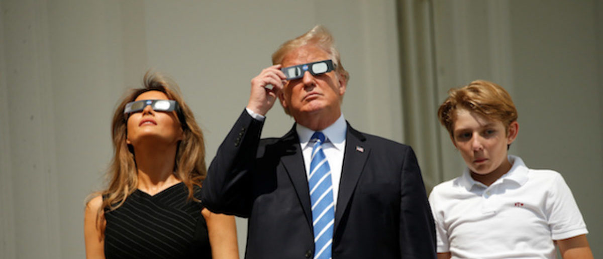 U.S. President Donald Trump watches the solar eclipse with first Lady Melania Trump and son Barron from the Truman Balcony at the White House in Washington, U.S., August 21, 2017. REUTERS/Kevin Lamarque - RTS1CPAK