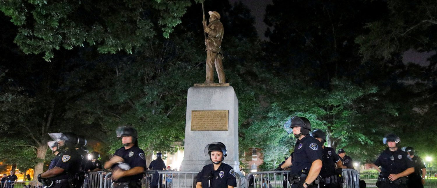 Police wearing riot gear guard a statue of a Confederate soldier nicknamed Silent Sam on the campus of the University of North Carolina during a demonstration for its removal in Chapel Hill, North Carolina, U.S. August 22, 2017. REUTERS/Jonathan Drake TPX IMAGES OF THE DAY - RTS1CWNO