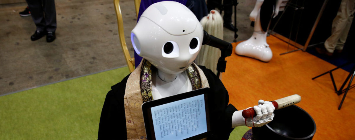 A 'robot priest' wearing a Buddhist robe chants sutras at it beats a wooden fish during its demonstration at Life Ending Industry EXPO 2017 in Tokyo, Japan August 23, 2017. REUTERS/Kim Kyung-Hoon - RTS1CXL3