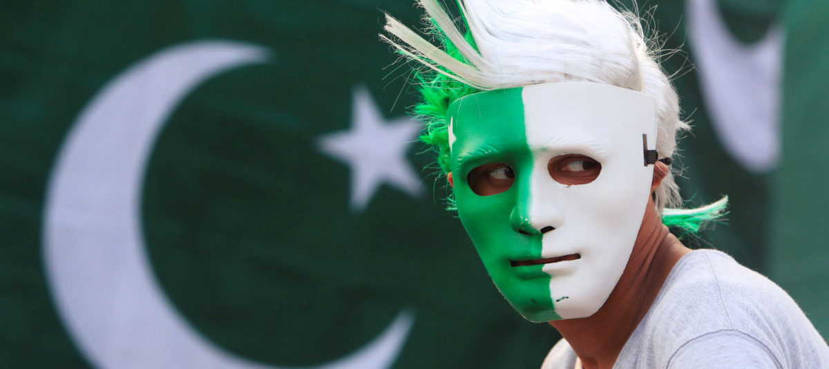 A vendor wears a mask with the colours of the Pakistani flag as people prepare to celebrate the country's Independence Day on August 14 at a roadside stall in Islamabad, Pakistan, August 10, 2016. REUTERS/Faisal Mahmood - RTSMDX3