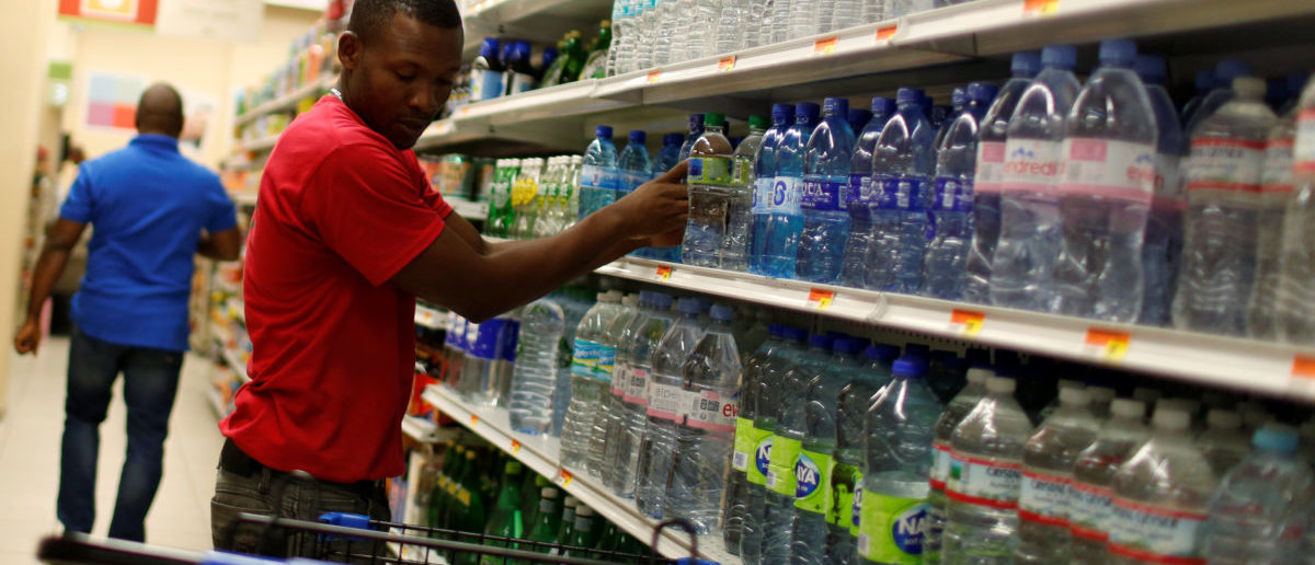 A supermarket employee puts water bottles on a shopping cart while people take care of their last minute shopping as Hurricane Matthew approaches in Port-au-Prince, Haiti