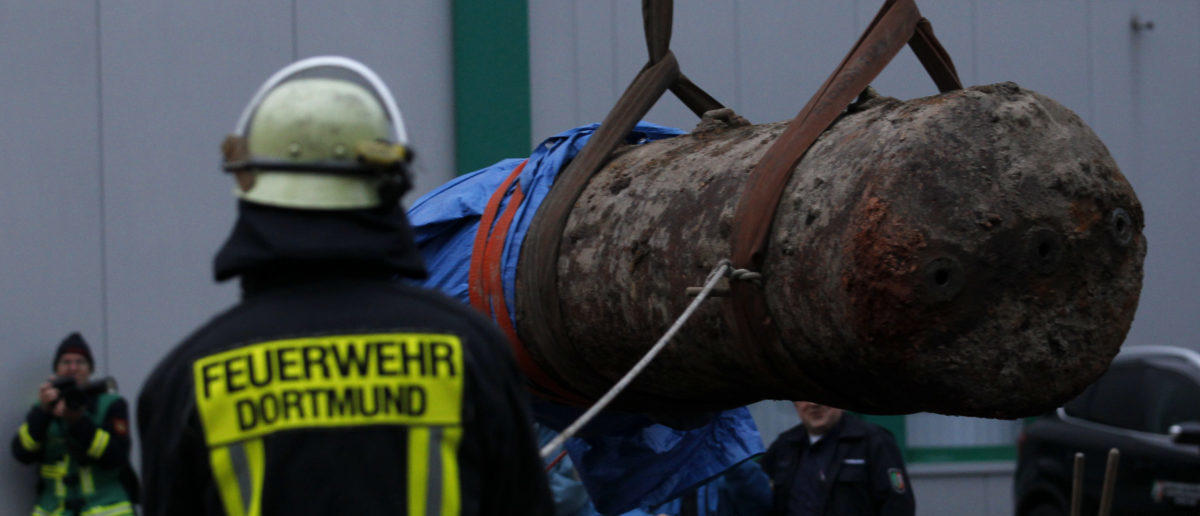 A member of Dortmund's Fire Department watches as a World War Two 1.8-ton (4000-lb) HC unexploded ordnance is removed after being successfully defused in Dortmund November 3, 2013. Some 20,000 people within a 1.5-km (0.93-mile) radius of the site where the ordnance was discovered via aerial photography last week, were evacuated on Sunday to enable the bomb disposal. The bomb had been dropped by the British Royal Air Force (RAF) during World War Two. REUTERS/Ina Fassbender