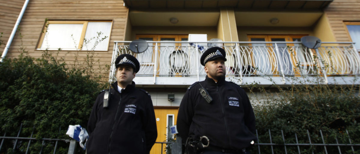 """Police stand guard in front of a property in Lambeth, south London November 23, 2013. Three women enslaved in London for 30 years appeared to have been part of a cult and bound to their captors by """"invisible handcuffs"""" through beatings and brainwashing, police said on Saturday. REUTERS/Luke MacGregor"""