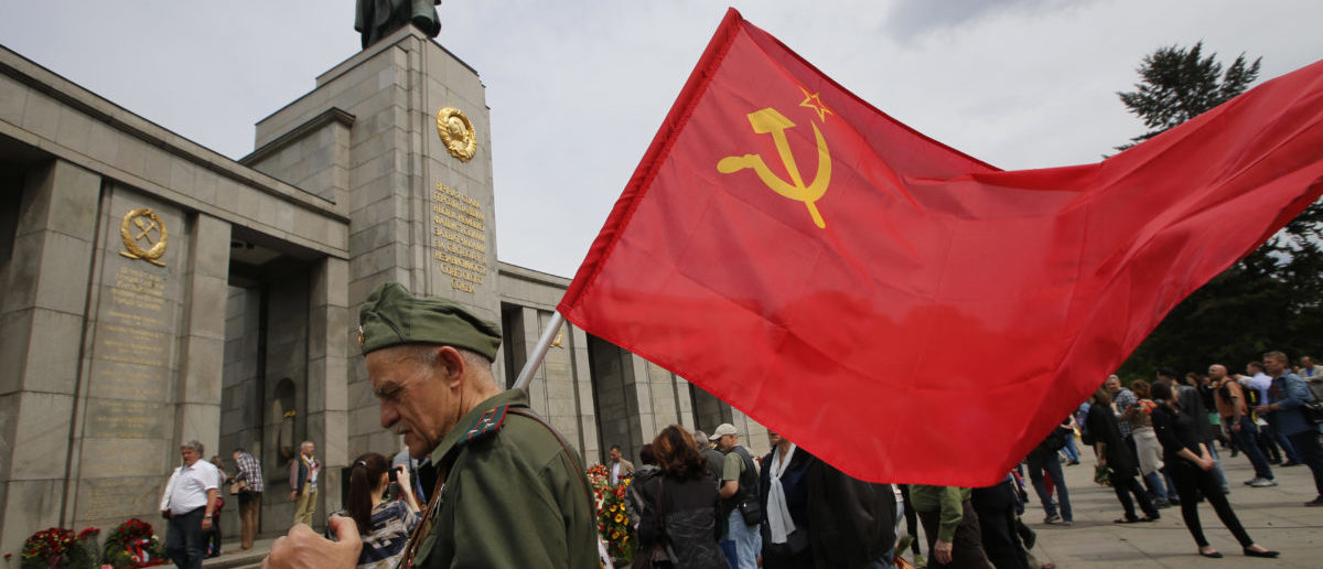 A man waering a Red Army uniform holds a Soviet flag during celebrations to mark Victory Day at the Soviet War Memorial near the Reichstag building, in Tiergarten district of Berlin, Germany, May 9, 2015.  REUTERS/Fabrizio Bensch TPX IMAGES OF THE DAY - RTX1C801