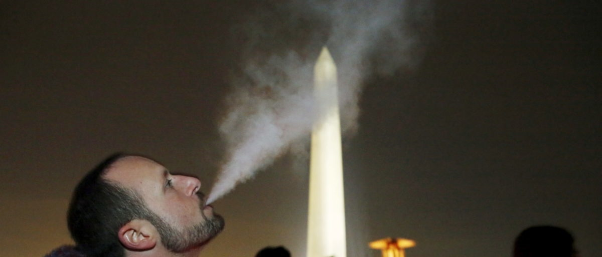 "Participant Ian Kreer exhales from an e-cigarette in front of the Washington Monument during a 48-hour vigil called ""Catharsis on the Mall: A Vigil for Healing the Drug War"" on the U.S. National Mall in Washington November 21, 2015. Participants burned an interactive art piece called the ""Temple of Essence"" dedicated to ""victims of the war on drugs."" REUTERS/Jim Bourg"