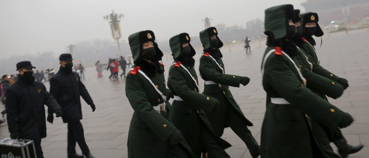 Paramilitary policemen wearing masks march on a cold morning following a flag-raising ceremony amid heavy smog at Tiananmen Square in Beijing