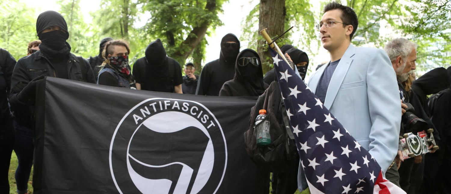 A conservative protester (R) walks past a group of anti-fascist during competing demonstrations in Portland, Oregon, U.S. June 4, 2017. REUTERS/Jim Urquhart TPX IMAGES OF THE DAY - RTX3904D