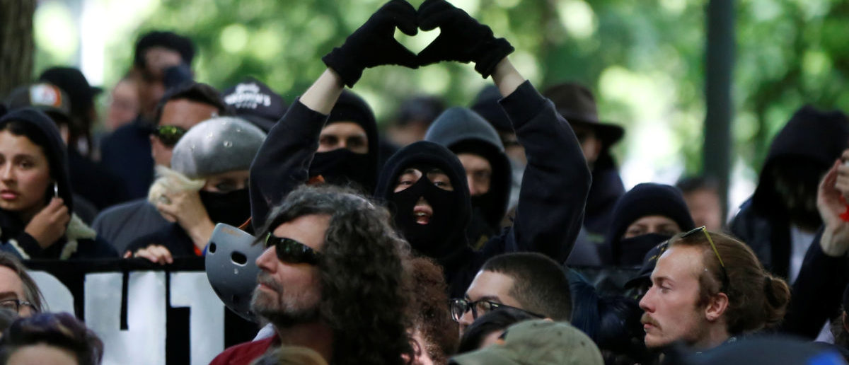 An anti-facist protester makes the heart symbol during competing demonstrations in Portland, Oregon, U.S. June 4, 2017.  REUTERS/Jim Urquhart