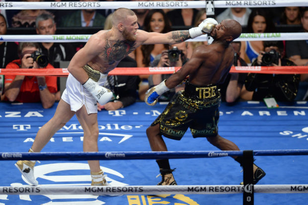 Aug 26, 2017; Las Vegas, NV, USA; Floyd Mayweather Jr. (black trunks) and Conor McGregor (white trunks) box during the fifth round of their boxing match at T-Mobile Arena. Mayweather won via tenth round TKO. Mandatory Credit: Joe Camporeale-USA TODAY Sports - via Reuters - RTX3DHNL
